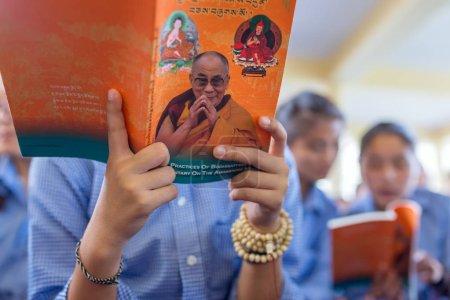 Dharamsala, India - June 6, 2017: Tibetan pupils listening to his Holiness the 14 Dalai Lama Tenzin Gyatso giving teachings in his residence in Dharamsala, India.