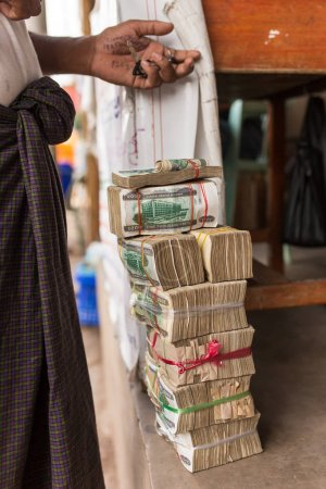 Hpa-An, Myanmar - October 21, 2017: Stacks of Myanmar money kyats in illegal exchange point on the border of Burma