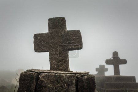 Old christian cemetery in Meghalaya, Northeast India. Silhouette of cross on cloudy day.
