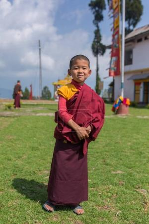 Pelling, India - April 26, 2017: Unidentified young novice buddhist monk in traditional red robes standing in front of a monastery in Pelling, Sikkim, India
