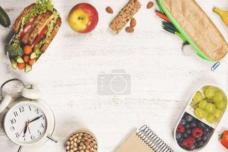 Foto de Sandwich, manzana, uva, zanahoria, baya en loncheras de plástico, papelería y botella de agua sobre fondo blanco. Regreso al concepto escolar . - Imagen libre de derechos