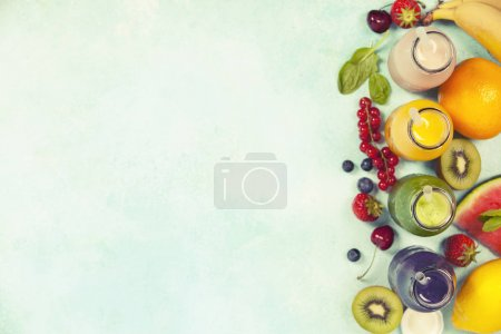Photo for Fresh juices or smoothies with fruits and vegetables on blue background, top view, selective focus. Detox, dieting, clean eating, vegetarian, vegan, fitness, healthy lifestyle concept - Royalty Free Image