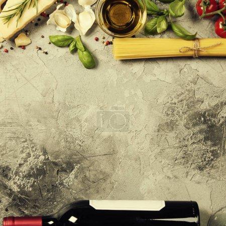 Photo pour Fond alimentaire italien avec raviolis, tomates de vigne, basilic, spaghetti, épinards, oignon, parmesan, huile d'olive, ail, grains de poivre, romarin et vin. Ardoise fond - image libre de droit