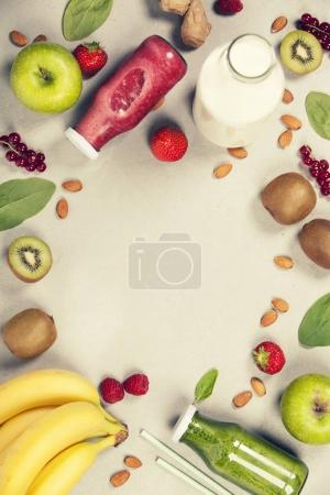 Photo for Green and red fresh juices or smoothies with fruit, greens, vegetables on grey background, top view, selective focus. Detox, dieting, clean eating, vegetarian, vegan, fitness, healthy lifestyle concept - Royalty Free Image