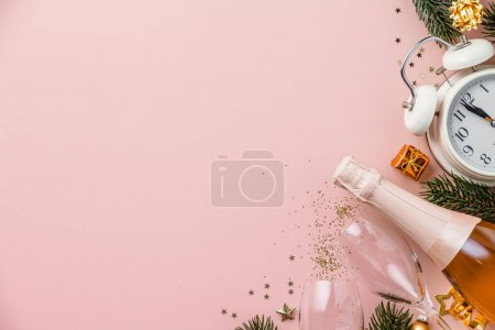 Photo for Christmas or New Year composition on pink background with retro alarm clock, bottle of champagne, glasses and Christmas decorations - stars, confetti, balls and gift boxes, top view, flat lay - Royalty Free Image