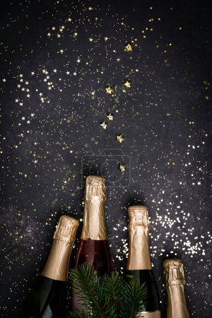 Photo for Bottles of champagne with gold glitter and space for text on dark background, top view. Hilarious celebration - Royalty Free Image