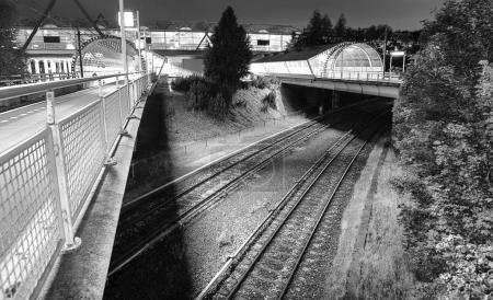 Railway or railroad tracks for train transportation at night time. Black-white photo.