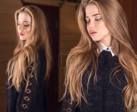 Elegant young beauty woman in luxury dress posing indoor against mirror.