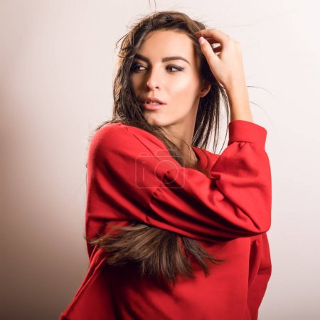 Young sensual model woman in red pose in studio.