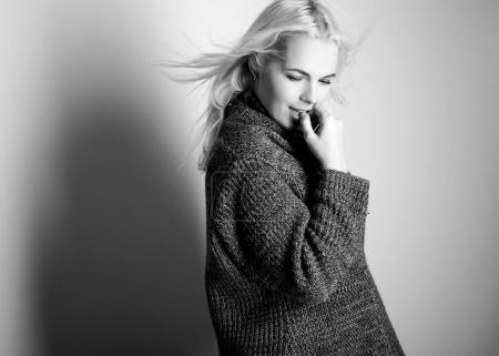 Photo for Young blond sensual model in a knitted sweater pose in studio. Black-white photo. - Royalty Free Image