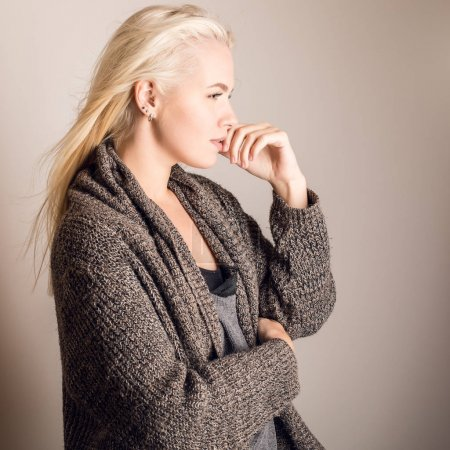 Young blond sensual model in a knitted sweater pose in studio.