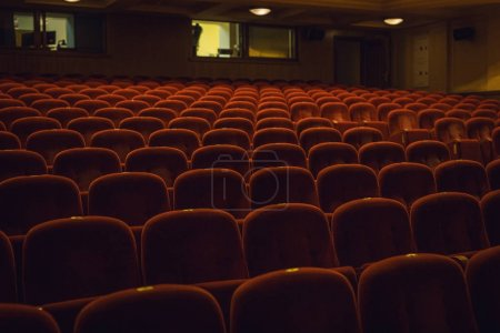 Red armchairs of old theater as conceptual background.