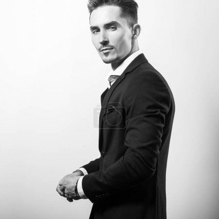 Handsome young elegant man in black stylish classic costume pose against studio background.