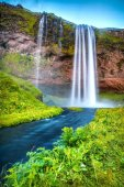 Picturesque landscape of a mountain waterfall and traditional nature of Iceland.