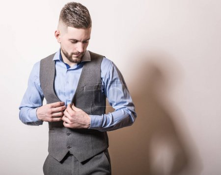 Photo for Handsome young elegant man in grey classic vest pose against studio background. - Royalty Free Image