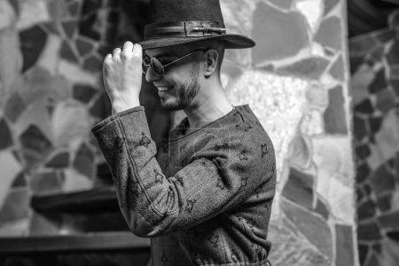 Handsome young stylish man in long coat and hat against stone background.