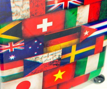 Photo pour Drapeaux internationaux imprimés sur un bagage. Concept de tourisme. - image libre de droit