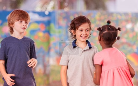 Mixed race classmates playing in schoolyard