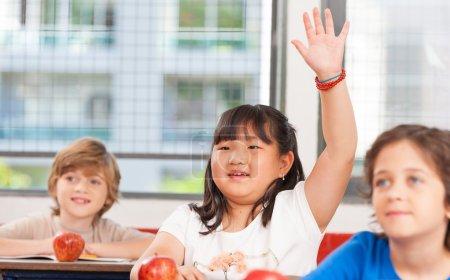 Schoolchild raising hand in classroom. Education concept