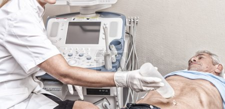 Mature man undergoing belly ultrasound with female doctor
