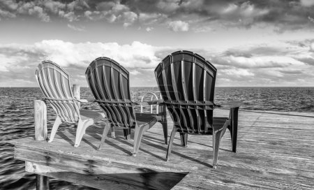 Black and white view of chairs on a wooden pier