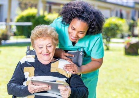 Nurse explaining tablet use to elder woman on wheelchair