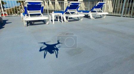 Drone shadow near beach chairs