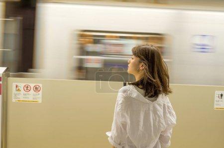 Mujer asiática esperando tren subterráneo en la estación