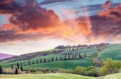 Panoramic sunset of of famous hill of cypresses in Tuscany, Ital