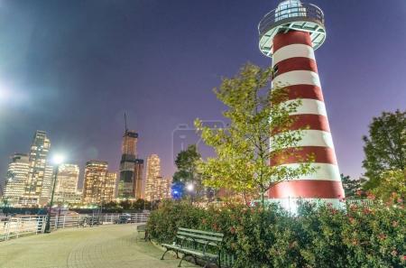 Lefrak Point Lighthouse and Jersey City skyline at night