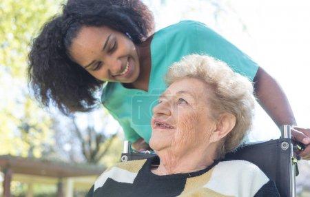 Nurse speaking to elderly woman in hospital garden