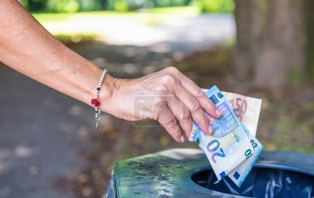 Photo for Woman's hand throwing money in public trashcan. Richness and business concept. - Royalty Free Image