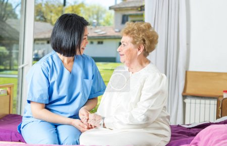 Nurse speaking with elderly woman in hospital bed