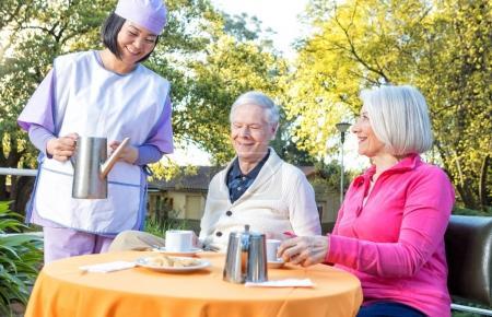 Elderly couple making breakfast outdoor served by asian nurse