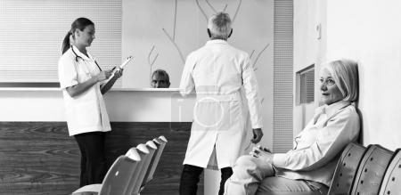 Doctors and patient discussing in hospital waiting room