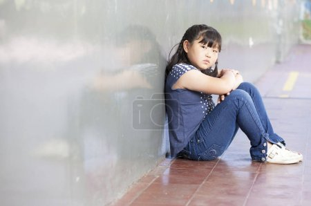 Asian schoolgirl alone in a school corner. Bullying concept