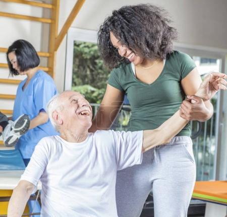 Elderly people in rehab clinic making gymnastics with the help o