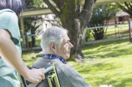Elderly male patient on wheelchair helped by nurse