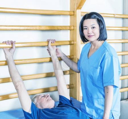 Asian nurse helping elderly male patient in rehab gym