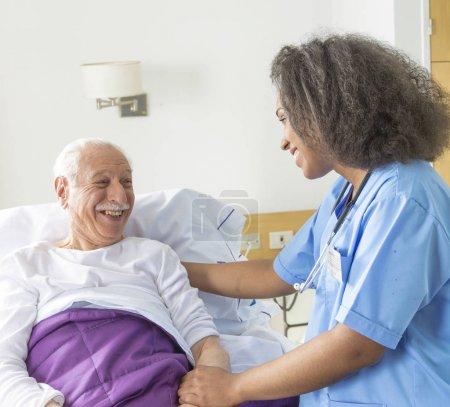 Reassuring confident african female doctor visiting elderly cauc