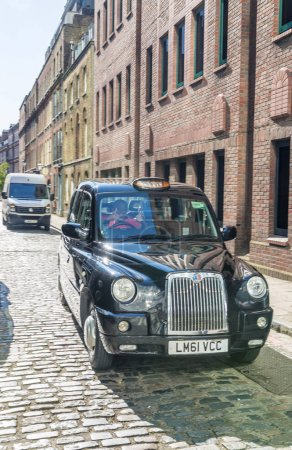 LONDON - MAY 2013: Black cab along old city street. London attra