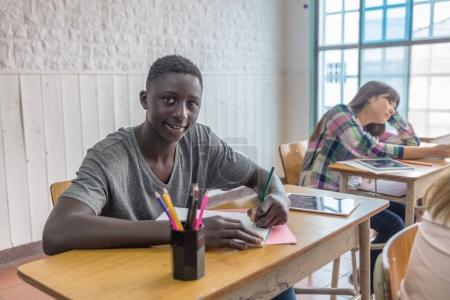 African male teenager making lesson in the classroom and happy about the test.