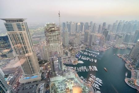 Aerial view of Dubai Marina skyline and docked boats at sunset.