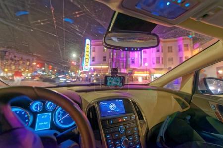 Driving along city traffic at night, view from car interior.