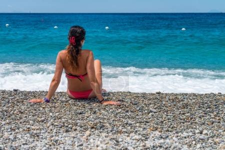 Beautiful woman looking at the ocean from the beach, back view. Travel concept.