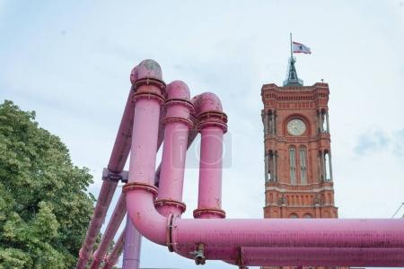 Colourful pink outdoor pipelines with valves, Berlin. Red Town Hall in background.