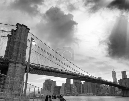 Black and white view of Brooklyn Bridge and Downtown Manhattan at sunset.
