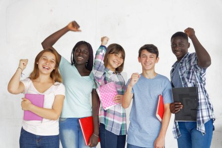 Multi ethnic teenagers smiling at school, raising arms, isolated on white background.