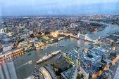 """Постер, картина, фотообои """"Тауэрский мост и горизонты города вдоль реки Темзы в ночное время, воздушные вид - Лондон - Великобритания."""""""