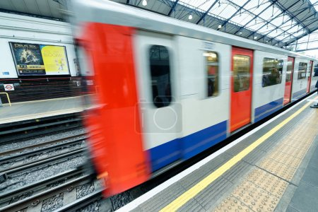LONDON - SEPTEMBER 26, 2016: Train speeds up in city subway. The system has 270 stations and 250 miles of tracks.